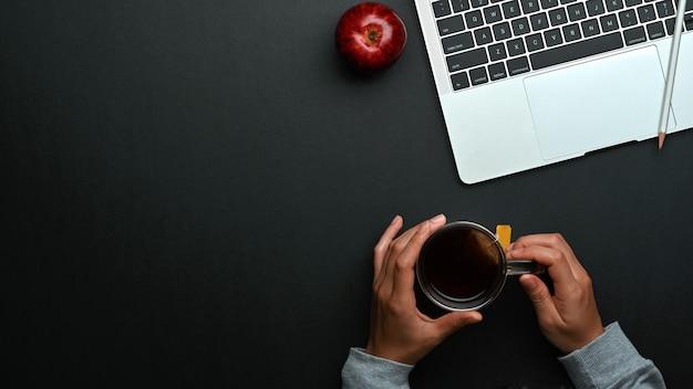 Vista dall'alto delle mani maschii che tengono tazza di caffè sulla tavola nera con lo spazio del computer portatile, della mela e della copia