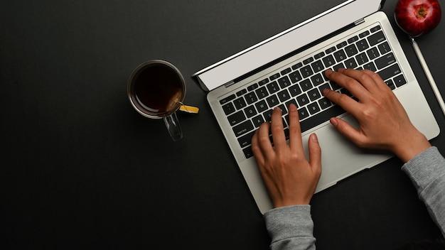 Vista dall'alto delle mani maschii che digitano sulla tastiera del computer portatile sulla tavola nera nella stanza dell'home office