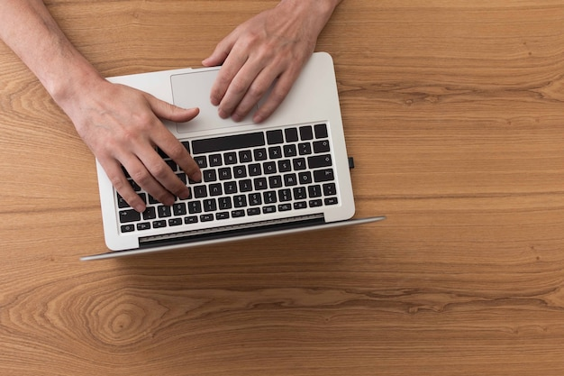 Vista dall'alto sulle mani maschili usando il laptop