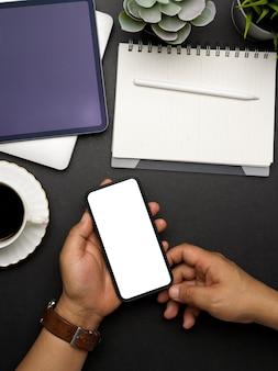 Vista dall'alto delle mani maschile utilizzando smartphone con mock up dello schermo su un'area di lavoro creativa scura, tracciato di ritaglio