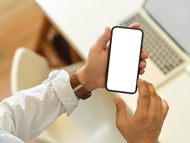 Vista dall'alto delle mani maschile utilizzando smartphone con schermo sopra l'area di lavoro
