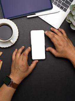 Vista dall'alto delle mani maschili che lavorano su smartphone con mock up schermo su area di lavoro creativa scura, tracciato di ritaglio