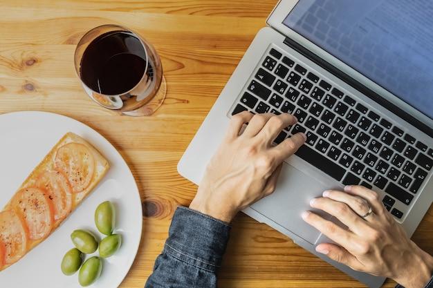 Vista dall'alto delle mani maschili che lavorano con il computer portatile durante la serata leggera pane, olive e vino. piatto concetto laico di lavorare sul computer a cena in cucina