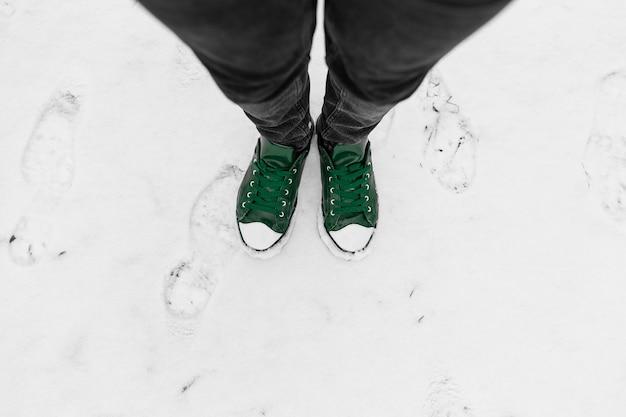 Vista dall'alto di gambe maschili che indossano jeans neri e scarpe da ginnastica vintage verdi, in piedi sulla neve all'aperto. selfie di piedi.