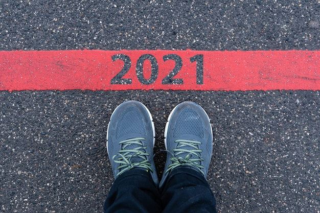 Vista dall'alto di scarpe da ginnastica maschili sulla strada asfaltata con testo 2021 sulla linea rossa, concetto di celebrazione del nuovo anno Foto Premium