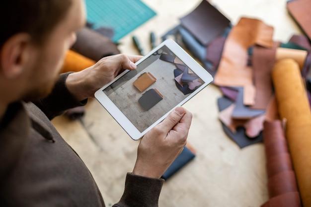 Il conciatore maschio vista dall'alto usa il tablet presso l'artigiano del laboratorio di pelle che crea promozione pubblicitaria online
