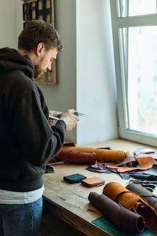 Il conciatore maschio vista dall'alto usa il tablet presso l'artigiano del laboratorio di pelletteria che crea promozione pubblicitaria online