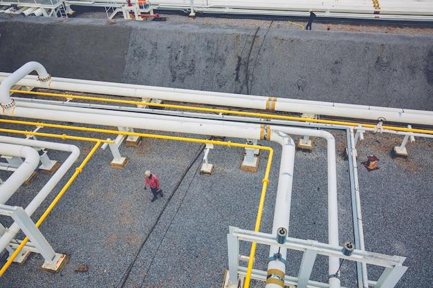 Vista dall'alto lavoratore maschio in acciaio tubi lunghi e fabbrica di valvole durante la raffineria industria petrolchimica nella distilleria del sito di gas e petrolio
