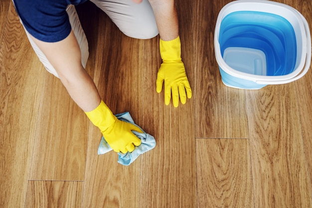 Vista dall'alto dell'uomo che pulisce il parquet a casa. ha guanti di gomma sulle mani. accanto a lui c'è un secchio con detersivo.