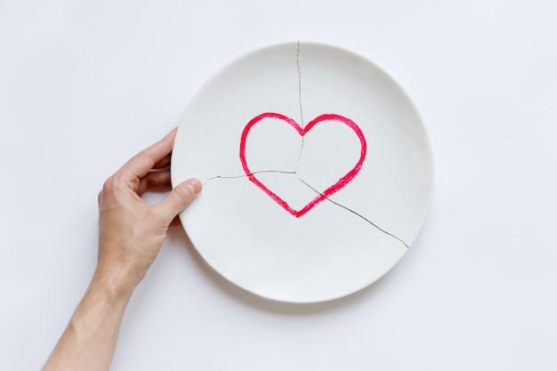 Vista superiore della mano dell'uomo che tiene un piatto bianco rotto con il simbolo del cuore. metafora di divorzio, relazioni, amicizie, crack nel matrimonio. l'amore se n'è andato