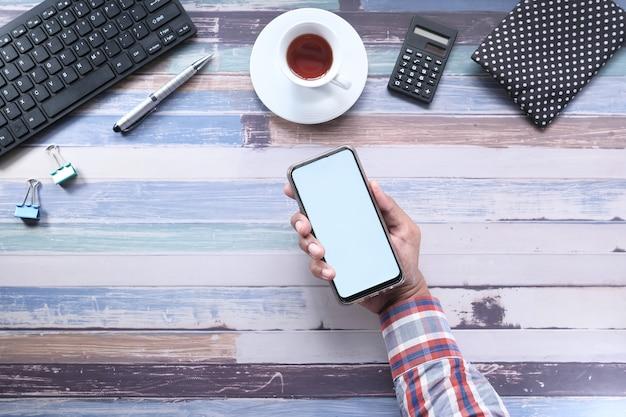 Vista superiore dello smart phone della tenuta della mano dell'uomo con lo schermo vuoto sulla scrivania