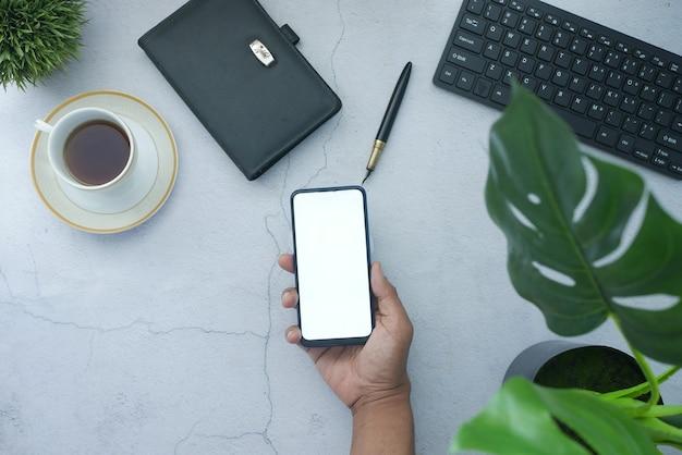 Vista dall'alto dello smartphone che tiene la mano dell'uomo con lo schermo vuoto sulla scrivania dell'ufficio