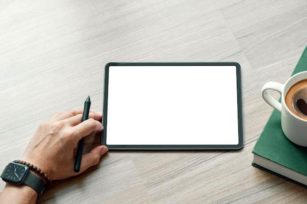 Vista dall'alto della mano dell'uomo che tiene la penna stilo e il tablet con schermo vuoto.
