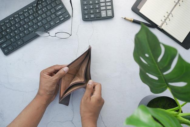 La vista dall'alto della mano dell'uomo apre un portafoglio vuoto sul tavolo