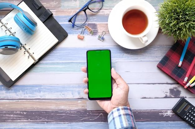 Vista superiore della mano dell'uomo utilizzando smart phone sulla scrivania in ufficio