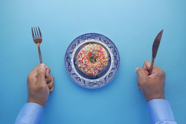 Vista dall'alto della mano dell'uomo con coltello e forchetta per mangiare ciambelle