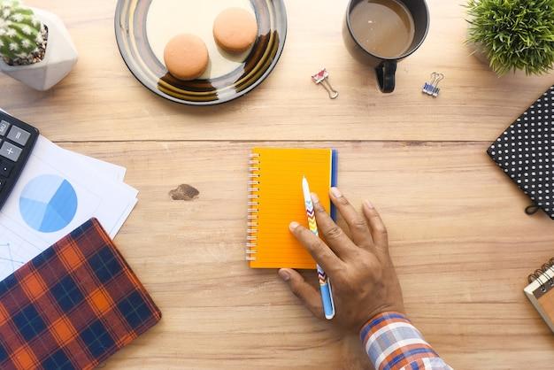 Vista dall'alto della mano dell'uomo che scrive sul blocco note sulla scrivania in ufficio