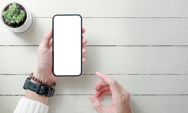 Vista dall'alto delle mani dell'uomo che tengono smartphone a schermo vuoto, schermo vuoto per la visualizzazione del prodotto.