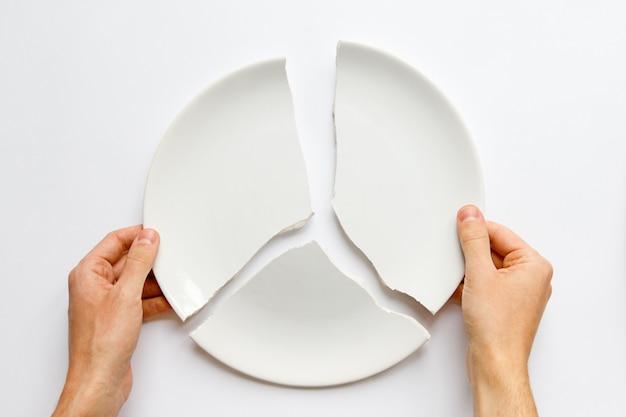 Vista superiore delle mani dell'uomo che tengono un piatto bianco rotto. metafora di divorzio, relazioni, amicizie, crack nel matrimonio. l'amore se n'è andato