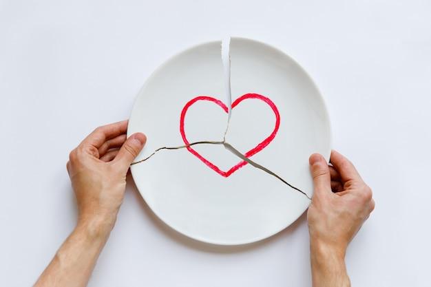 Vista superiore delle mani dell'uomo che tengono un piatto bianco rotto con il simbolo del cuore. metafora di divorzio, relazioni, amicizie, crack nel matrimonio. l'amore se n'è andato