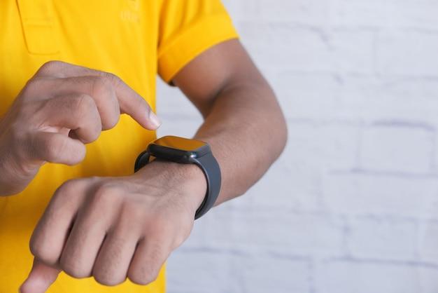 Vista dall'alto della mano dell'uomo utilizzando smart watch.