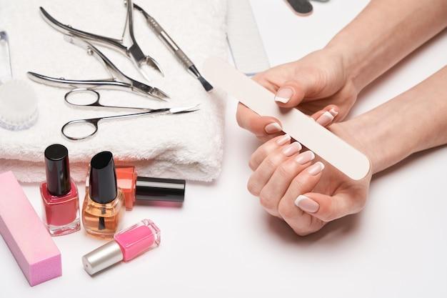 Vista dall'alto del set di strumenti per manicure per la cura delle unghie su una superficie chiara: pennello, forbici, smalto per unghie, lima e pinzette