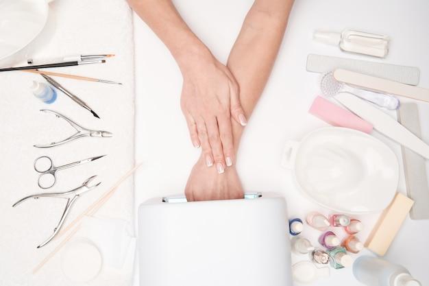 Vista dall'alto di strumenti per manicure e donna che prepara le sue mani per ottenere la procedura di manicure