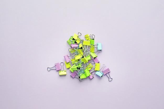 Vista dall'alto di molte clip di raccoglitori multicolore su sfondo viola pastello. colori al neon alla moda.