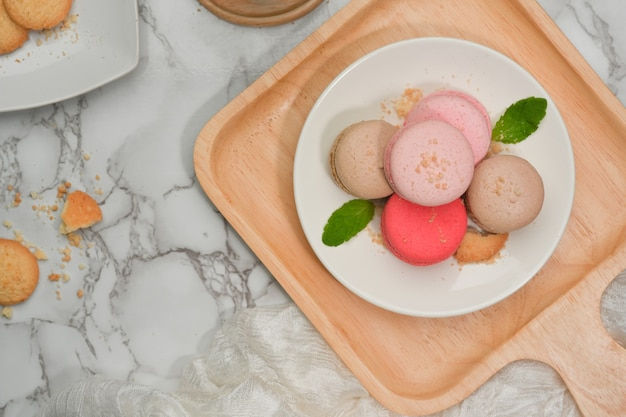 Vista dall'alto del tavolo da pranzo in marmo con un piatto di macarons colorati francesi e un piatto di biscotti
