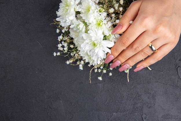 Vista dall'alto proposta di matrimonio concetto mano femminile con fiori ad anello su sfondo scuro spazio libero