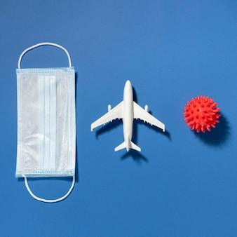 Vista dall'alto della mascherina medica con la figurina dell'aeroplano e il virus