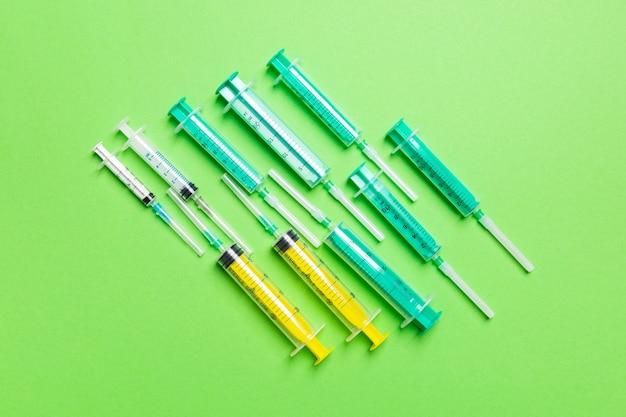 Vista dall'alto di siringhe mediche con aghi a sfondo verde con spazio di copia. concetto di trattamento di iniezione.