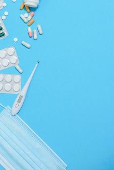 Vista dall'alto di medicinali, strumenti di lavoro e accessori medico, infermiere. set medico - compresse, termometro, siringa, fiale, cerotto adesivo e statoscopio su sfondo blu. lay piatto
