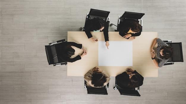 Vista dall'alto del tavolo da conferenza in legno per riunioni con sei donne d'affari dirigenti sedute su ciascuna sedia che discutono e parlano di affari nel lavoro di squadra nella sala riunioni.