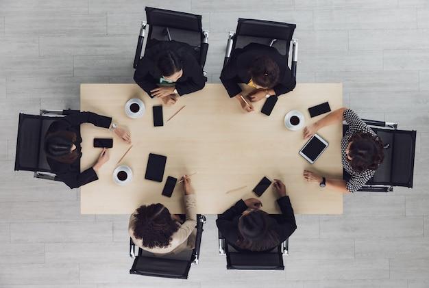 Vista dall'alto del tavolo da conferenza in legno con sei dirigenti d'affari seduti su ogni sedia che discutono e parlano di affari nel lavoro di squadra con i telefoni cellulari sul tavolo nella sala riunioni.