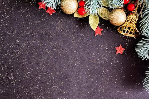 Vista dall'alto buon natale sfondo nero decorato con rami di alberi e palline d'oro, stelle rosse con spazio di copia.