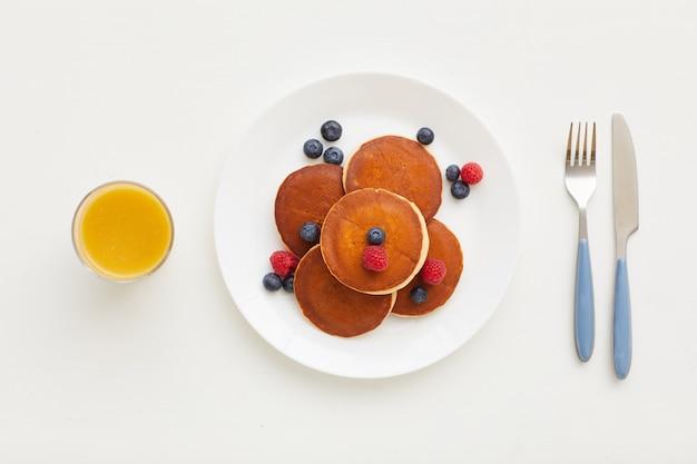 Vista dall'alto alla composizione minima di deliziose frittelle dorate con frutti di bosco freschi accanto a succo d'arancia e coltello e forchetta, concetto di colazione