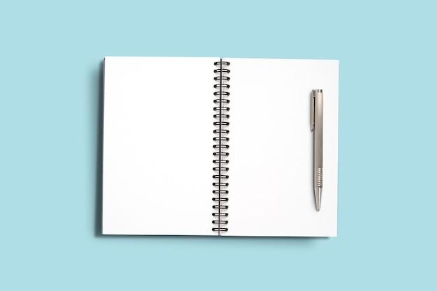 Vista dall'alto design minimale di memo notebook aperto con matita rosa su sfondo blu.