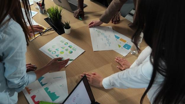 Vista dall'alto gruppo di persone di razza mista ufficio piccola impresa start up azienda che pianifica riunioni creative utilizzando tablet digitali che mostrano dati finanziari e grafici