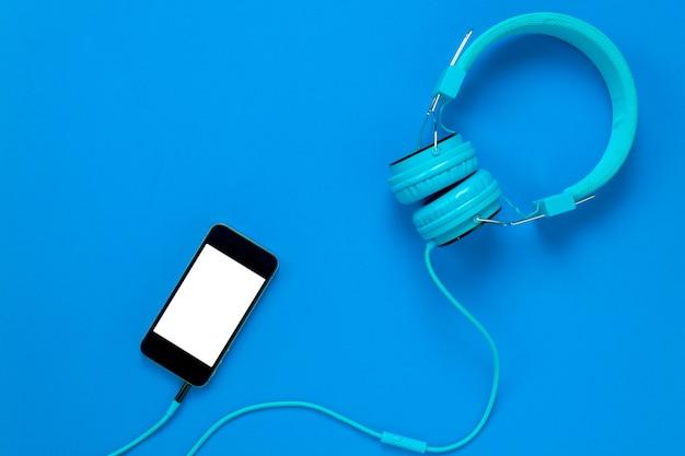 Vista superiore telefono cellulare e cuffie su sfondo blu con spazio di copia.