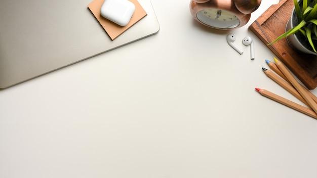 Vista dall'alto della scena di simulazione con decorazioni di cancelleria per laptop e spazio di copia sulla scrivania bianca