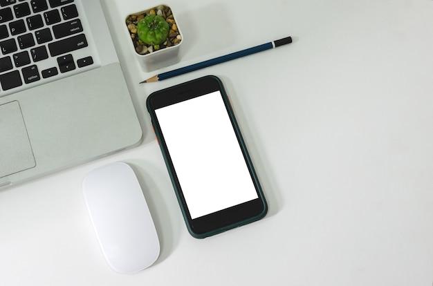 Vista dall'alto mock up smart phone bianco schermo vuoto e matita mouse computer portatile piatto adagiato sulla scrivania.