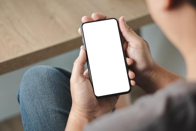 Vista dall'alto mockup immagine mano utilizzando un telefono cellulare con cellulare uomo con schermo vuoto
