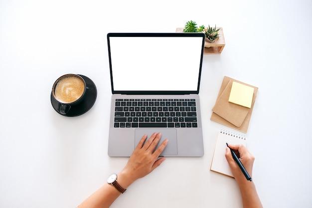 Immagine mockup vista dall'alto di una donna che utilizza un laptop con uno schermo desktop bianco vuoto mentre scrive su un notebook