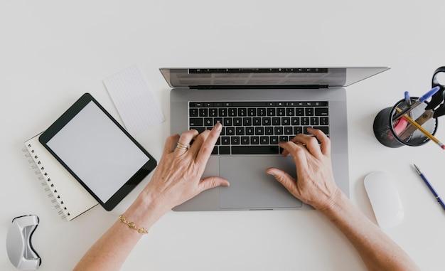 Vista superiore della compressa e della persona del modello che scrivono sul computer portatile