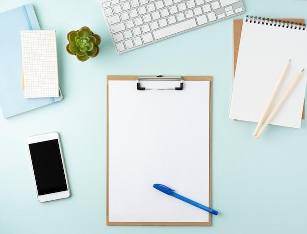 Vista dall'alto moderno desktop ufficio blu con blocco note vuoto