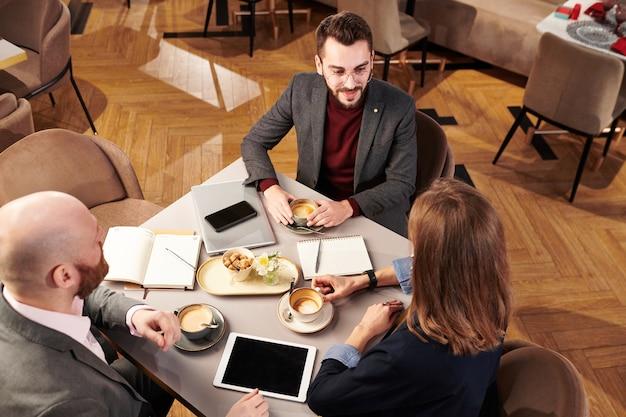 Vista dall'alto di uomini d'affari moderni seduti al tavolo con blocchi di appunti e lavorando su un progetto di business nel ristorante