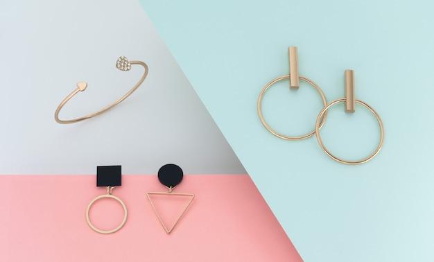 Vista dall'alto della coppia di orecchini dal design geometrico moderno su sfondo di carta con spazio di copia