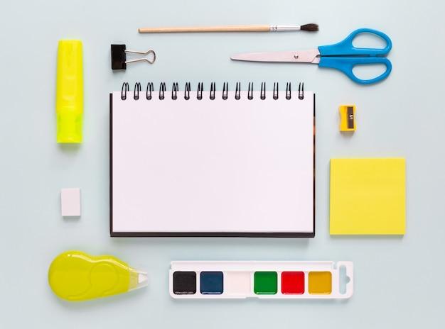 Vista dall'alto del moderno desktop da ufficio bianco blu con materiale scolastico e cancelleria sul tavolo intorno allo spazio vuoto per il testo. ritorno al concetto di scuola disteso con mockup