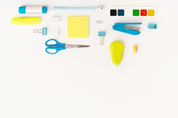 Vista dall'alto del moderno desktop da ufficio bianco, blu, giallo con materiale scolastico e cancelleria sul tavolo intorno allo spazio vuoto diagonale per il testo. ritorno al concetto di scuola disteso con mockup